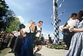 Junge Männer und Frauen tanzen um den Maibaum, Maibaumfest in Holzhausen, Feste in Bayern, Bayern, Deutschland