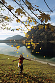 Teenage girl throwing autumn foliage in the air, Sylvensteinspeicher lake, Bavaria, Germany