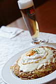 Close up of a roesti, potatoe dish, and a beer in Restaurant Hasenburg, Basel, Switzerland