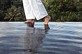 Man s feet on the edge of an outdoor pool at Losari Coffee Plantation in West Java, Indonesia, South East Asia