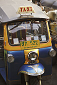 A Tuk Tuk - the famous three wheel taxi of Bangkok, notorious for its noise and pollution, waiting for customer at the roaside, Bangkok, Thailand, Southeast Asia