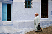 Woman walking in typical street in Chefchaouen, Morocco.