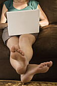 A young woman using a laptop on the sofa