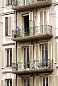 Elderly woman looking out from her balcony. Nice, France
