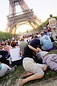 Couple kissing on grass near Eiffel tower. Paris. France