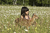 Girl with white tailed deer fawn in field of flowers