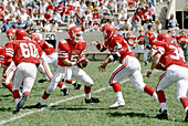High School football action quarterback, hands off ball to running back