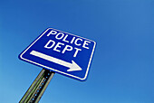 Street sign showing direction to a police department