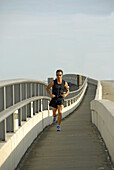 Adult male runs across a bridge in Jacksonville Florida for exercise and health. USA.