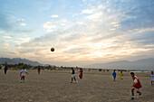 Boys playing football at sunset, Dibba, Oman