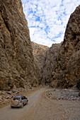 4x4 jeep driving through a canyon, dirt road, mountain landscape, Hajjar mountains, Musandam, Oman