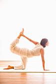 Mid adult woman practising yoga (Cat Pose), yoga studio at Linz, Austria
