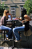 Two young women sitting in a cfafe in the historic centre of Ljubljana, Slovenia