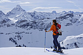Female backcountry skier enjoying view over Allgaeu Alps, Bavaria, Germany