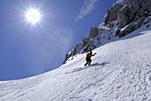 Female skier downhill skiing, Pyramidenspitze, Eggersgrinn, Zahmer Kaiser, Kaiser range, Tyrol, Austria