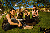 Young japanese women sitting in a meadow at Isle de la Cité at night, Paris, France, Europe