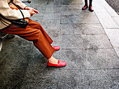 Adult, Adults, Anonymous, Bench, Benches, Color, Colour, Contemporary, Daytime, Exterior, Female, Gray, Grey, Horizontal, Human, Leg, Legs, Outdoor, Outdoors, Outside, Pair, Pavement, Pavements, People, Person, Persons, Seated, Sidewalk, Sidewalks, Sit, S