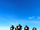 Adult, Adults, American football, Back view, Blue, Blue sky, Color, Colour, Companion, Companions, Compete, Competing, Competition, Competitions, Contemporary, Daytime, Exterior, Football, Game, Games, Horizontal, Human, Male, Man, Match, Matches, Mate, M