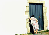 Adult, Adults, Back view, Closed, Color, Colour, Contemporary, Curiosity, Curious, Daytime, Door, Doors, Entrance, Entrances, Entries, Entry, Europe, Exterior, Female, Full-body, Full-length, Galicia, Horizontal, Human, Look, Looking, Mature Adult, Mature