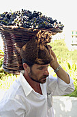 Man in traditional costume with typical grape basket. Festas das Vindimas (grape harvest festival). Estreito da Camara de Lobos. Madeira. Portugal.