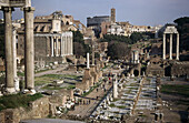 Saturn Temple (left), Via Sacra (centre), Temple of Castor and Pollux (right) and Colosseum (in background). Roman Forum, Rome, Italy