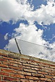 Blue, Blue sky, Brick, Bricks, Chainlink fence, Chainlink fences, Cloud, Clouds, Color, Colour, Daytime, Exterior, Fence, Fences, Low angle view, Outdoor, Outdoors, Outside, Protect, Protection, Security, Skies, Sky, View from below, Wall, Walls, Worms ey