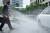 businessman gets splashed by a passing car