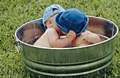 babies kissing in a metal tub