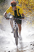 Man splashing through water on a mt. biking in Sun Valley, Idaho. USA