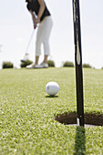 Aim, Aiming, Ball, Balls, Close up, Close-up, Closeup, Color, Colour, Concept, Concepts, Daytime, Detail, Details, Exterior, Golf, Golf course, Golf courses, Ground, Grounds, Hole, Holes, Human, Leisure, Object, Objects, One, One item, One person, Outdoor