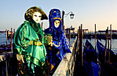 Two people on a small pier over Grand Canal dressed in lavish costumes and masks for the annual masquerade carnival in Venice, Italy