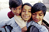 Three young Indian boys huddle together posing for the camera smiling.
