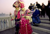 Two people in vivid colour costumes at masquerade in Venice, Italy