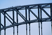 People walking across the top of the Sydney Harbor Bridge on a tourist attraction offered by BridgeClimb, Sydney, Australia.