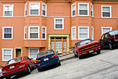 Cars parked in front of a bright, well-maintained orange house on a very steeply sloped section of Jones Street in San Francisco, California. The street is so steep that the sidewalk has steps.