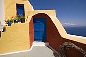 Yellow house, cascading flowerpots, blue door and sea view. Santorini. Greece