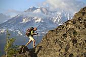 Man climbing a ridge while backpacking alone near Mount Adams Wilderness. Washington. USA