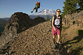 A man jumps off a rock while hiking on a trail near Mount Adams. Washington. USA