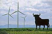 Bull silhouette, typical advertising of Spanish sherry Osborne, and wind turbines by windfarm. Zaragoza province, Aragón, Spain