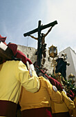 Penitents carrying float during Holy Week procession, Cuenca. Castilla-La Mancha, Spain