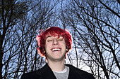 Teen boy, with dyed red hair, standing and posing outside