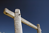 Weathered white wooden pylons against blue sky