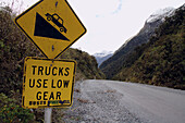 Trucks use low gear, buses freewheel. Sign at beginning of descent from Wilmot Pass, road to Doubtful Sound, Fiordland National Park, New Zealand