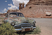 Antique, Asphalt, Automobile, Blue sky, Brush, Buick, Chrome grill, Color, Colour, Decrepit, Desert, Green auto fiour door, Headlights, Mountains hoodoos, Old, Red, Roadmaster, Rocks, Run down, Rust, N17-564164, agefotostock