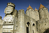 Statue of Madame Carcas welcomes to La Cité, Carcassonne medieval fortified town. Aude, Languedoc-Roussillon, France