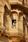 Rajasthani man looking out a window surrounded by an ornate facade at the Mehrangarh Fort, Jodhpur, Rajasthan, India