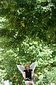 Engel, junge Frau mit Engelsflügeln beim Fahrradfahren, München, Bayern, Deutschland