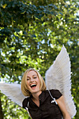 Mid adult woman wearing angel wings laughing at camera