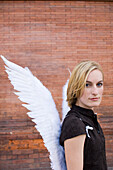 Mid adult woman wearing angel wings in front of a brick wall