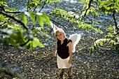 Mid adult woman wearing angel wings standing in lake Starnberg looking up, Bavaria, Germany